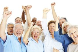 Happy group of senior citizens showing a thumbs up on white